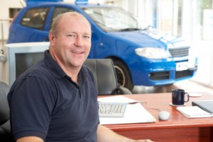Car salesman sitting in showroom smiling